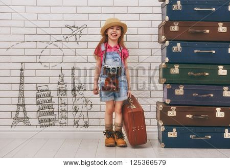 happy child girl against a white brick wall. girl having suitcases and dreaming of traveling.
