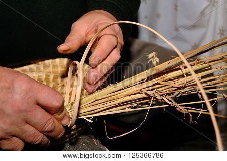Person weaves traditional wicker basket - close-up