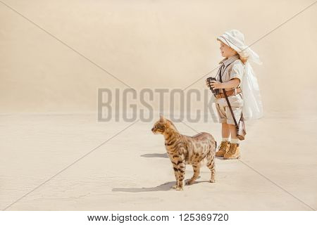 Concept of travel and fascinating adventures. hild in suit of treasures seeker in the desert whit wild cat similar to tiger