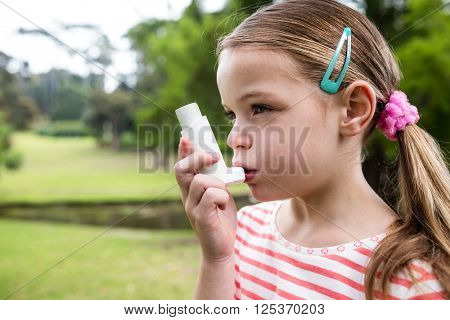 Girl using an asthma inhaler in the park