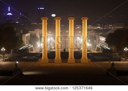 View From Palau Nacional Towards The Four Columns And Placa D Espanya At Night In Barcelona