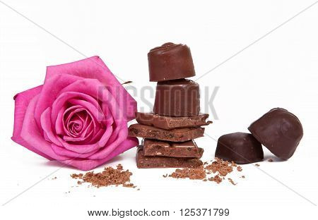 Chocolate candies background. Chocolate. Assortment of fine chocolates in white, dark and milk chocolate. Pink rose