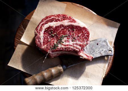 Bone In Rib Eye row Steak and knife for cutting meat on a wooden board.