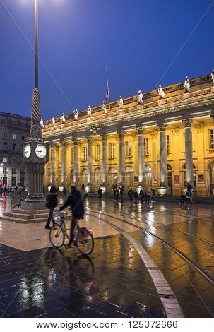 Bordeaux France - March 25 2016. Men in bike rolling in front of Grand Theatre de Bordeaux at night. The theatre is home to the Opera National de Bordeaux and the Ballet National de Bordeaux. Bordeaux Aquitaine. France.