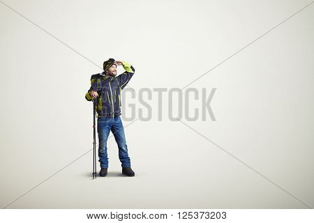 Man wear winter clothes with hiking poles and looking away, on white background