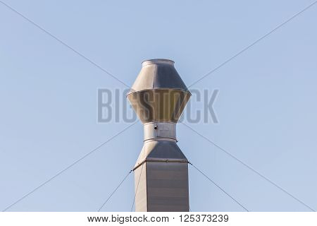 Single industrial chimney against clear blue sky. Metal smokestack of abandoned no working factory. Silver color isolated.
