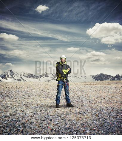 Man wear winter clothes and hard-hat and crossed his hands and stay in the mountains