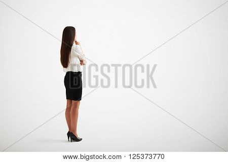 Young girl with long hair and wearing formal clothes touches to her chin, back view