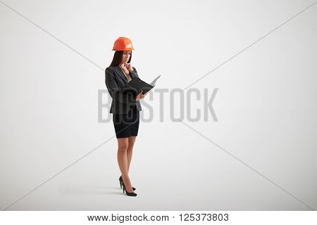 Standing woman in formal wear and construction helmet familiarize with the materials in black folder holding her hand near chin