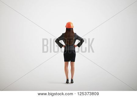 Back view of woman in formal wear and construction helmet with her arms akimbo