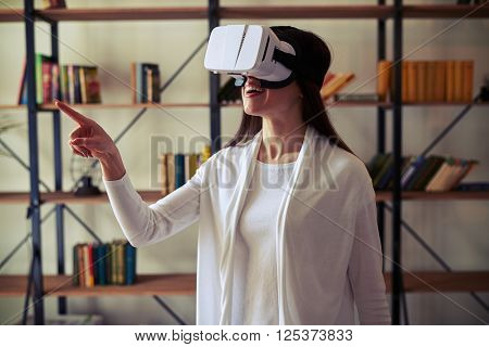 Beautiful Caucasian woman touch something using modern virtual reality glasses
