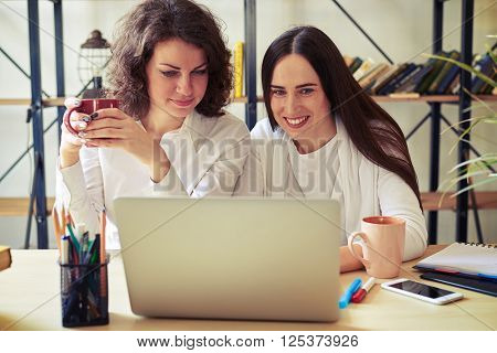 Two women sitting at the table and working at a laptop, one of them holding cup