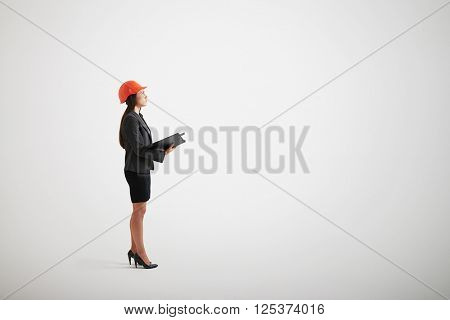 Serious woman in formal wear and hard hat looking up and holding opened black folder in her hands