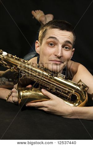 The Young Jazzman Lie On The Floor With Saxophone