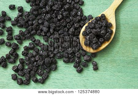 Dried chokeberry fruits (Aronia melanocarpa) in wooden spoon