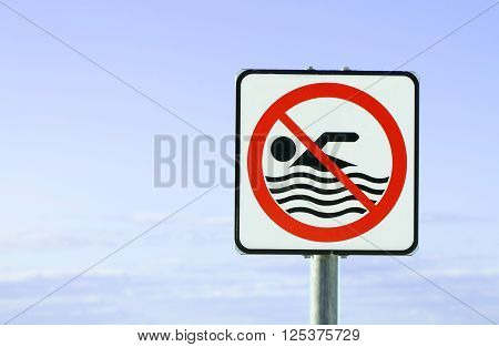 An European warning sign at the beach with man swim and not symbol Caution No Swimming allowed