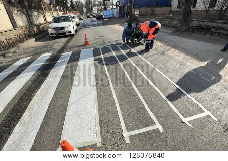 Saint-Petersburg Russia - April 6 2016: Road workers doing markup crosswalk with white paint