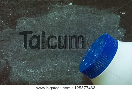 Talcum powder and write word talcum on black grunge background