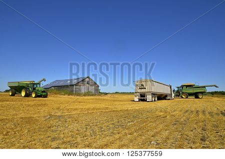 MAYVILLE, NORTH DAKOTA-August 19, 2015: A harvest scene of a tractor and grain cart cart,  products of John Deere Co, an American corporation that manufactures agricultural, construction, forestry machinery, and diesel engines.