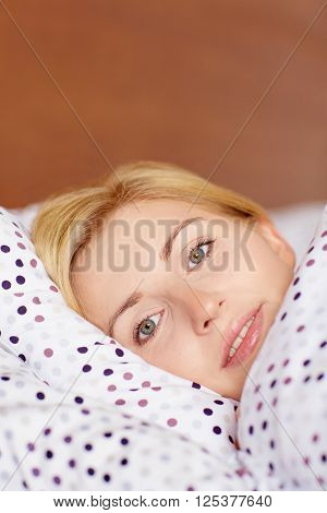 A young woman lying awake in her bed
