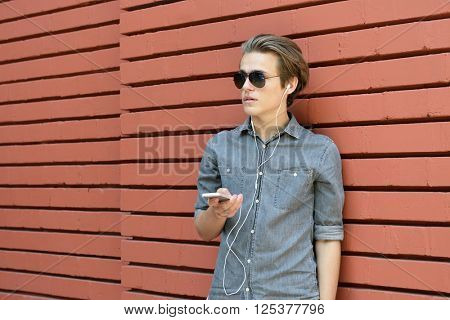 Young man having fun outdoor using smartphone against red brick wall. Urban lifestyle, internet and gadget dependence, loneliness, social network concept. Image toned and noise added.