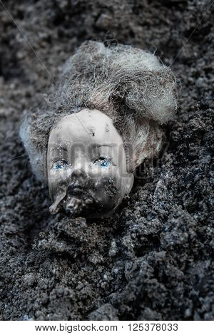 Plastic burnt girl doll head lying in a pile of grey ash
