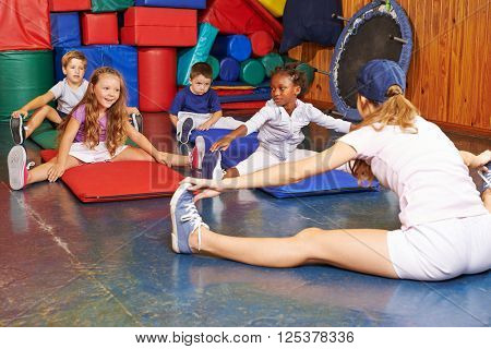 Children exercising in physical education with sports teacher