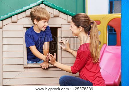 Happy mother and son playing a clapping game in nursery at home