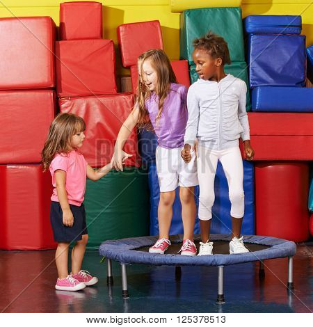Three children jumping on a trampoline in gym