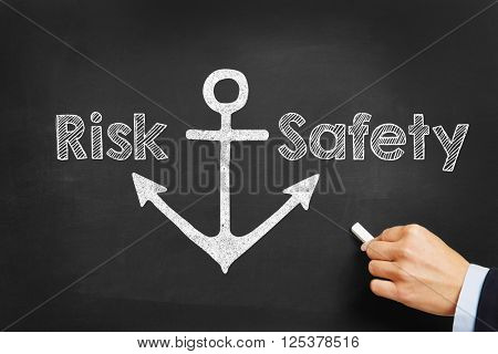 Hand with chalk writing decision between risk and safety concept on blackboard