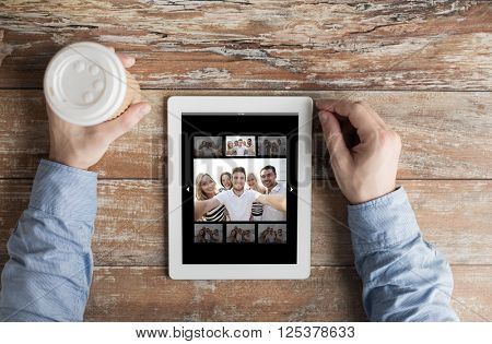 people, memory and technology concept - close up of male hands with picture of happy friends on tablet pc computer screen and coffee cup at table