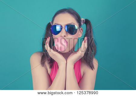 Beautiful surprised fashion funny model girl wearing sunglasses with bubble of chewing gum