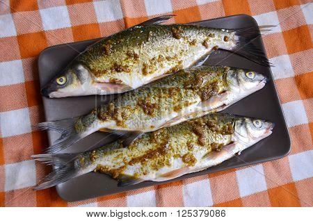 Three raw marinade fish (vimba bream) on the plate