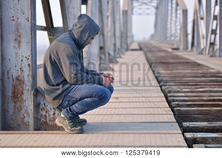 Thinker Teenager In Depression Sitting Down On The Bridge At The Sunset. Concept Of Teenage Problems