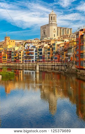 Saint Mary Cathedral, colorful yellow and orange houses and famous white house Casa Maso reflected in water river Onyar, in Girona, Catalonia, Spain.