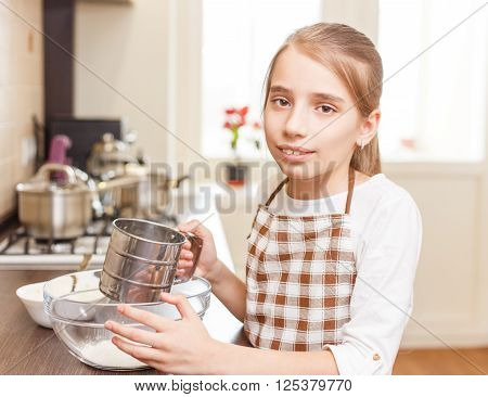 Small Girl In Apron Holding Sieve Preparing Flour