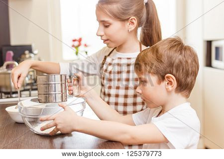 Small Girl With Her Brother Put Flour Into Sieve