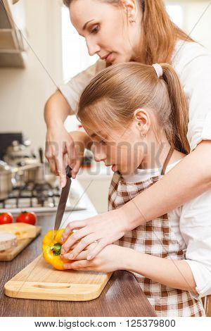 Young Woman Teaching Her Daughter Cut Vegetables