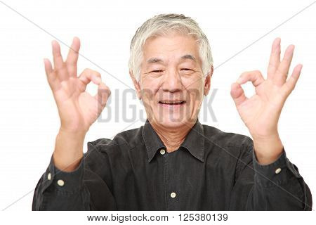portrait of senior Japanese man showing perfect sign