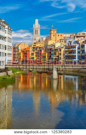 Church of Sant Feliu, colorful yellow and orange houses and bridge Pont de Sant Agusti reflected in water river Onyar, in Girona, Catalonia, Spain