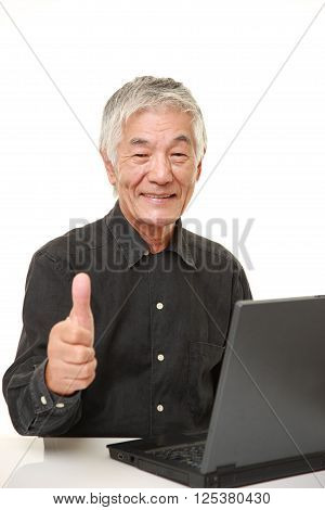 portrait of senior Japanese  man using laptop computer