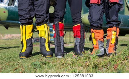 High Altitude Mountain Boots Three People Staying on Grassy Meadow with Cargo Helicopter on Background