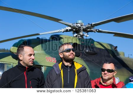 Group of Smiling Mountain Climbers Arrived to Exotic Destination by Helicopter Sporty Clothing Jacket Sunglasses