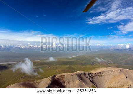 Central Asia Landscape Areal View from Helicopter Desert Hills on Foreground Grassy Meadows and High Snowbound Mountain Range Blue Sky Clouds