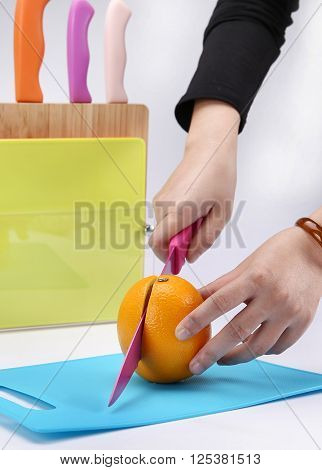 Girl cutting orange with the knife