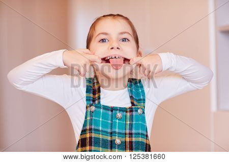 A cute little girl pulling a face on front of camera