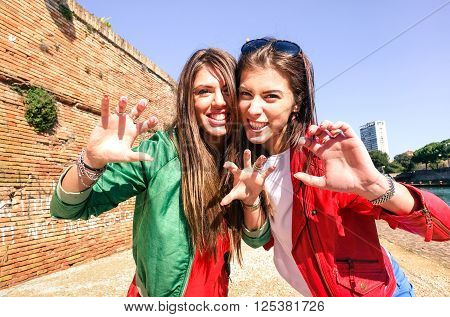 Cheerful best friend girls having fun roaring at photo camera outdoor - Young women gesture and funny face expression - Concept of female friendship joyful moment during holiday travel in summer time
