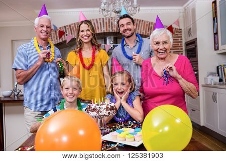 Multi-generation family in party hats having fun at birthday party
