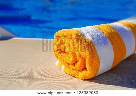 orange with white towel on a sun lounger on background of pool.