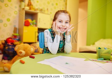 A happy little girl sitting at her table with art supplies